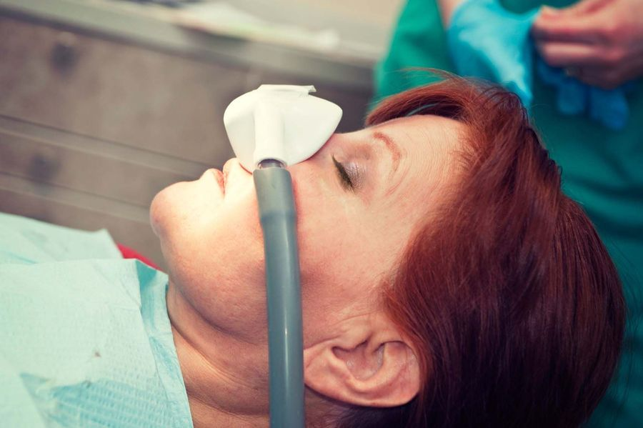 A woman wears a nitrous oxide mask as a method of sedation dentistry