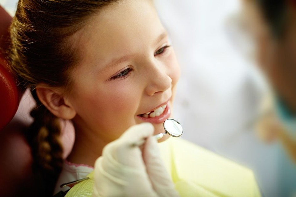 A young child undergoes a dental examination.