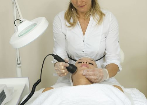 Woman lying down in while room receiving a laser resurfacing treatment