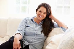 Heavyset, smiling woman in blue shirt reclining on couch