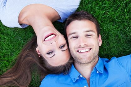 Playful couple lying down and posing on a green lawn with their heads together