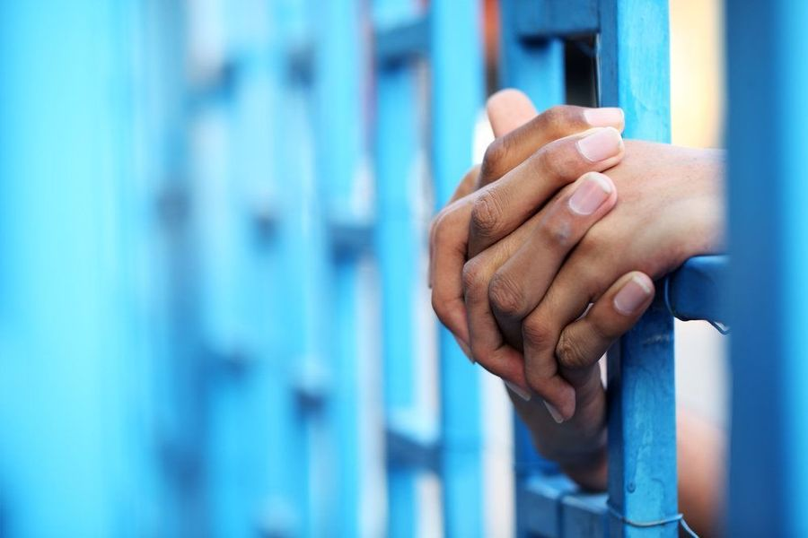 Hands interlocked through the bars of a jail cell.