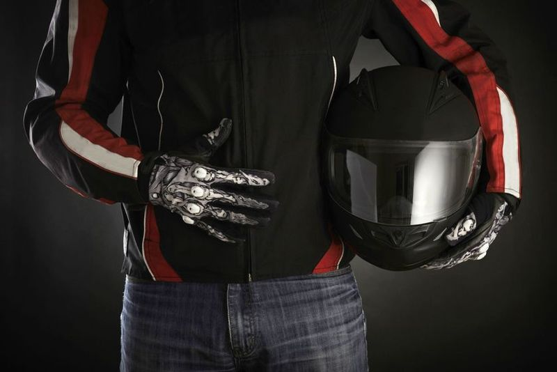 Man in motorcycle gear holding helmet