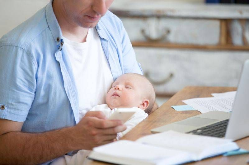Man holding newborn in front of computer