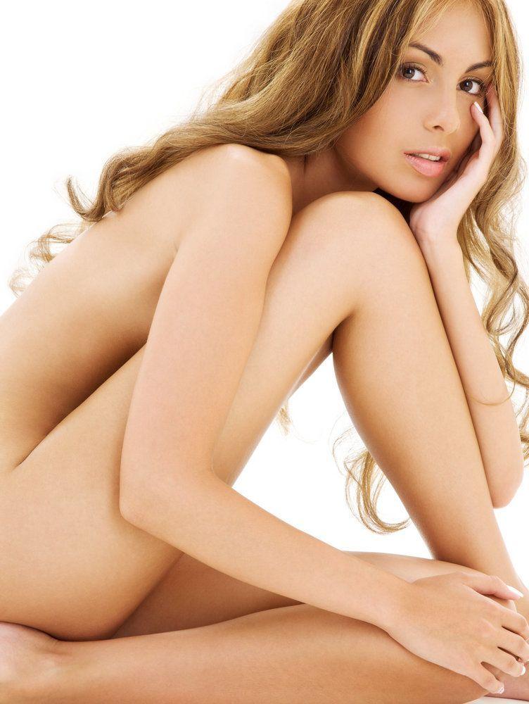 Una bella y desnuda mujer joven con largo cabello rubio oscuro se inclina sobre sus piernas, cubriendo discretamente sus áreas privadas.