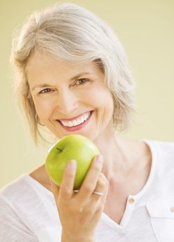 Elderly woman smiling while holding an apple