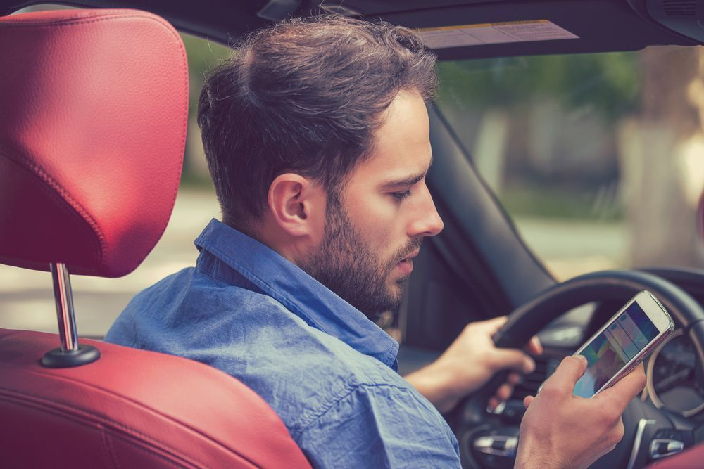 Photo of a man on his phone while driving