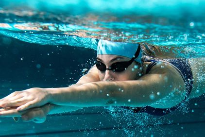 Woman in goggles swimming underwater