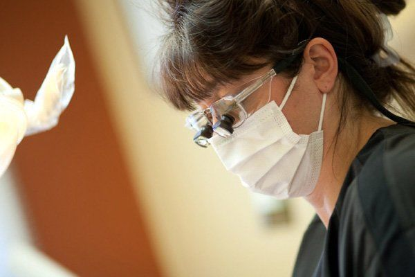 Dental assistant with magnified lenses and clinical mask