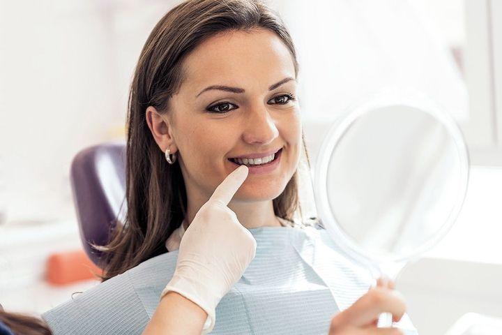 Smiling female dental patient looking in mirror