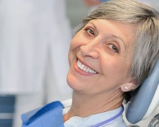 Grey-haired woman smiling in the dentist's chair