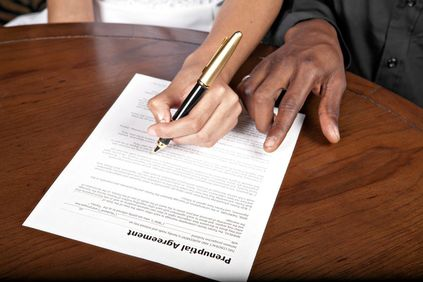 Photo of hand signing a prenuptial agreement