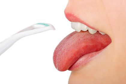 A patient holding out his/her tongue with a device nearby