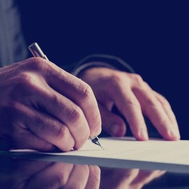 Hand with a pen signing a paper