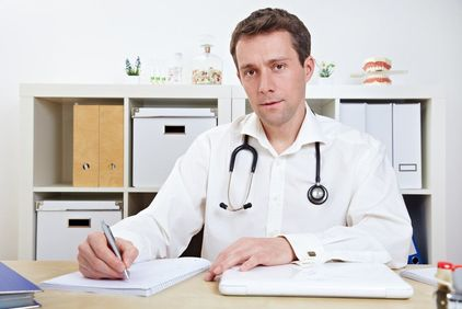Doctor writing on notepad at his desk