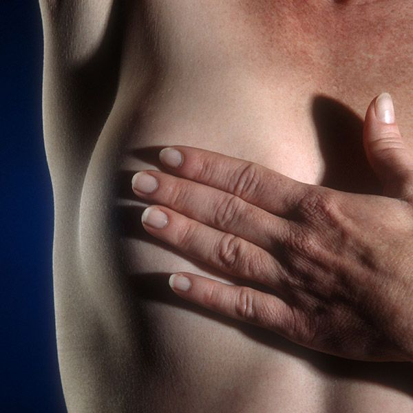 Woman holding hand over bare breast