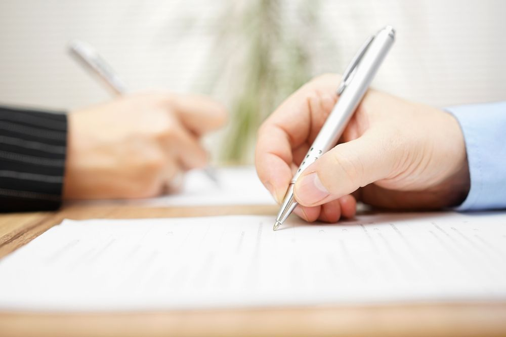 Close-up of hands signing divorce paperwork.