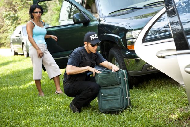 Police officer looking through a woman's suitcase.