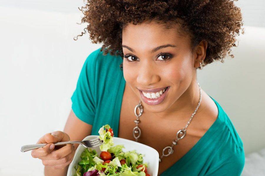 Smiling woman getting ready to eat salad