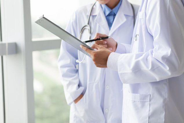 Two doctors confer about a patient's treatment