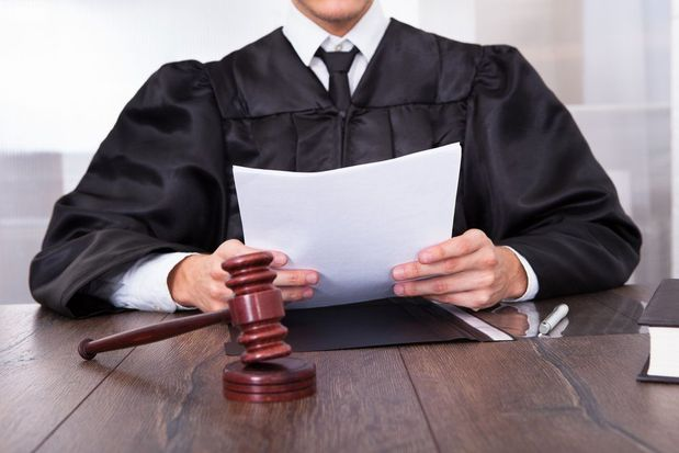 A judge at the bench reading a document.