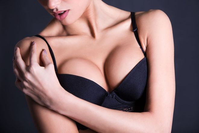 Woman in black bra crossing arms over chest
