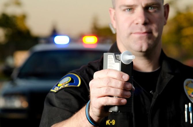 A police officer holding a breathalyzer machine