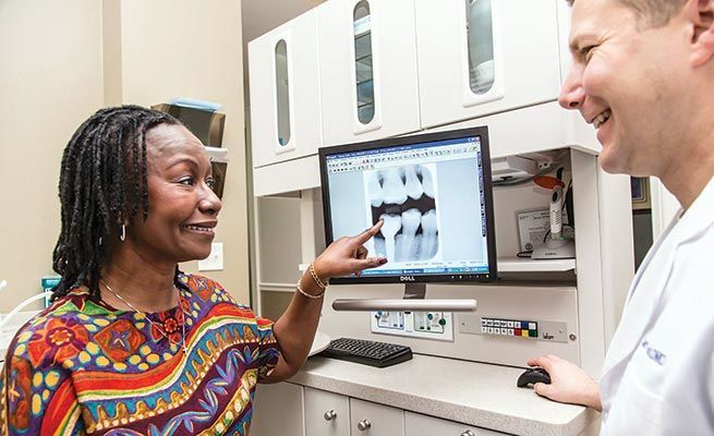 Woman pointing at a digital x-ray alongside Dr. Hancock