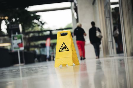 Yellow hazard sign on tile floor.