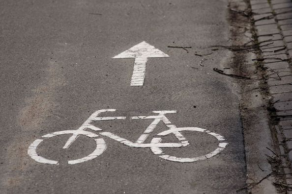 An arrow painted on the road with a bicycle symbol.