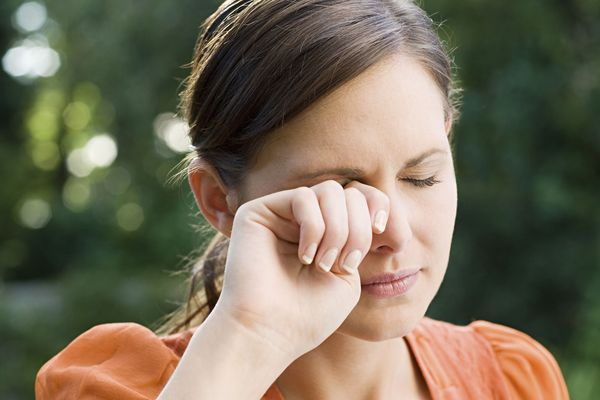 Woman rubbing her itchy eyes as a result of chronic dry eye.