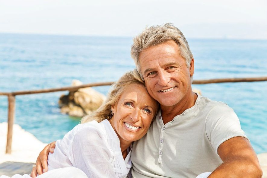 Tan smiling couple in front of the ocean