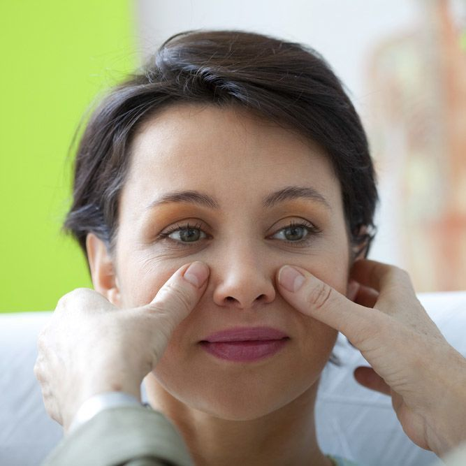 photo of a woman's nose being examined by Rhinoplasty Surgeon in Little Rock, AR