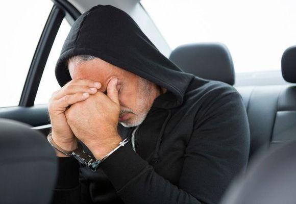Man in cop car holding head in hands