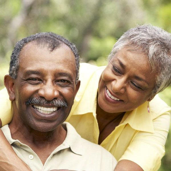 Elderly couple smiling after implants treatment