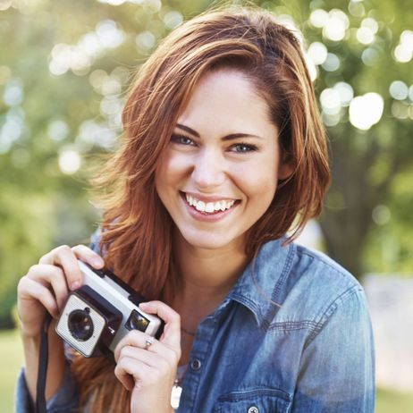 Young woman with a beautiful smile holding a camera