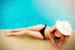 A fit woman relaxing by a pool