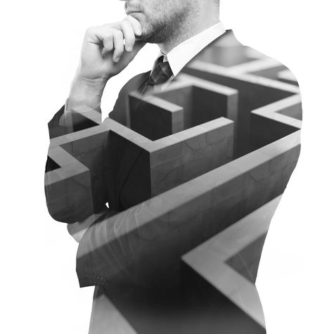 Black and white image of businessman with maze overlay