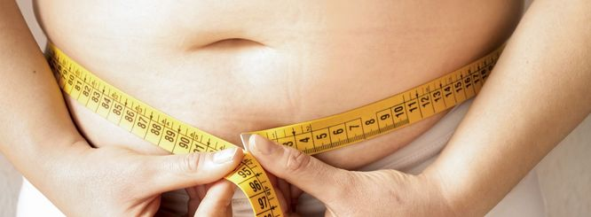 Photo of a person with measuring tape around their midsection