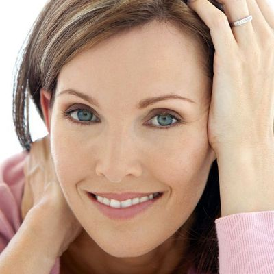 Facial Plastic Surgeon: Close-up of smiling woman brushing hair back from her face