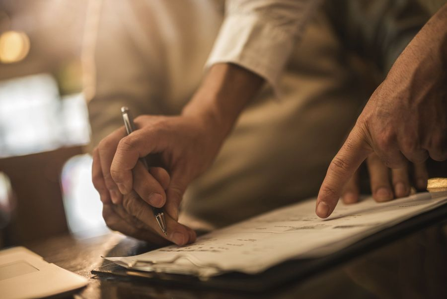 Man's hand guiding elderly man's hand to sign paperwork