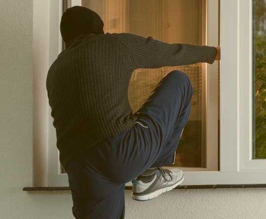 A burglar entering a home through a window