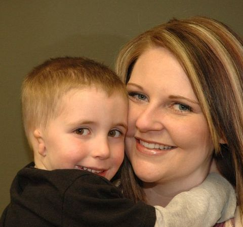 Son with misshapen ear being held by mother