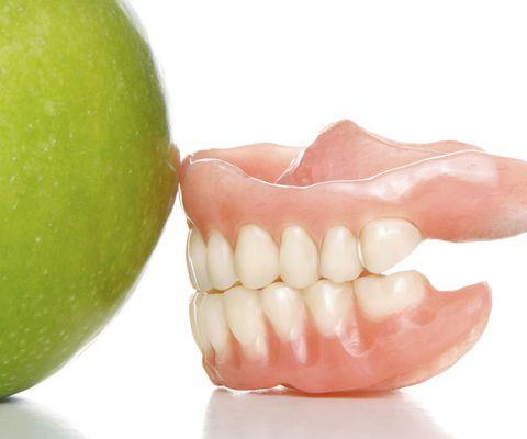 A set of dentures next to an apple