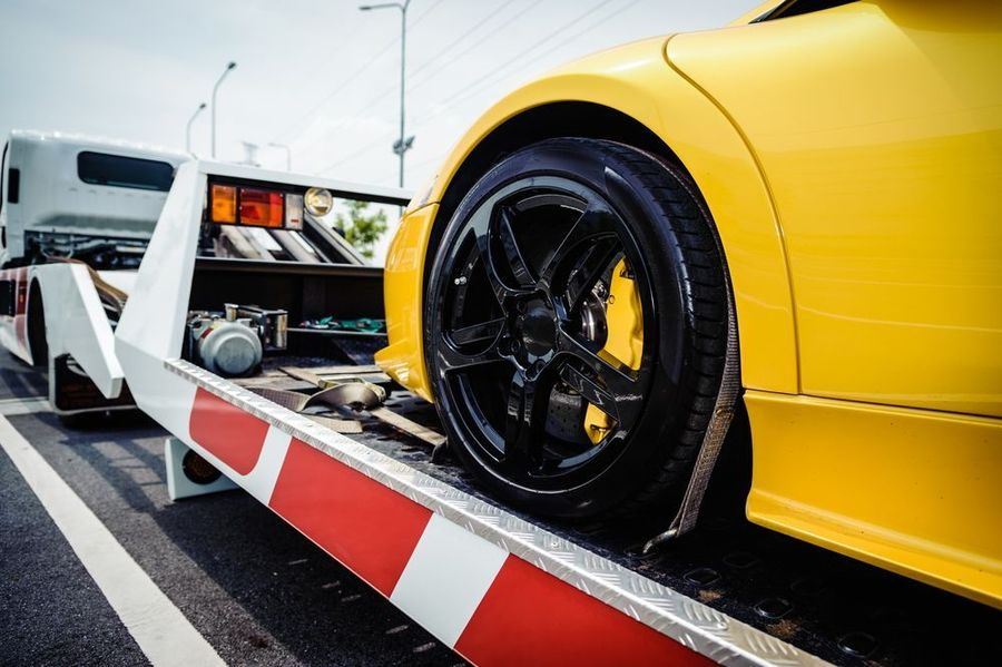 Yellow sports car being loaded onto tow truck