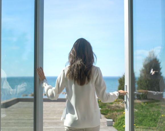 Woman looking out onto patio and ocean