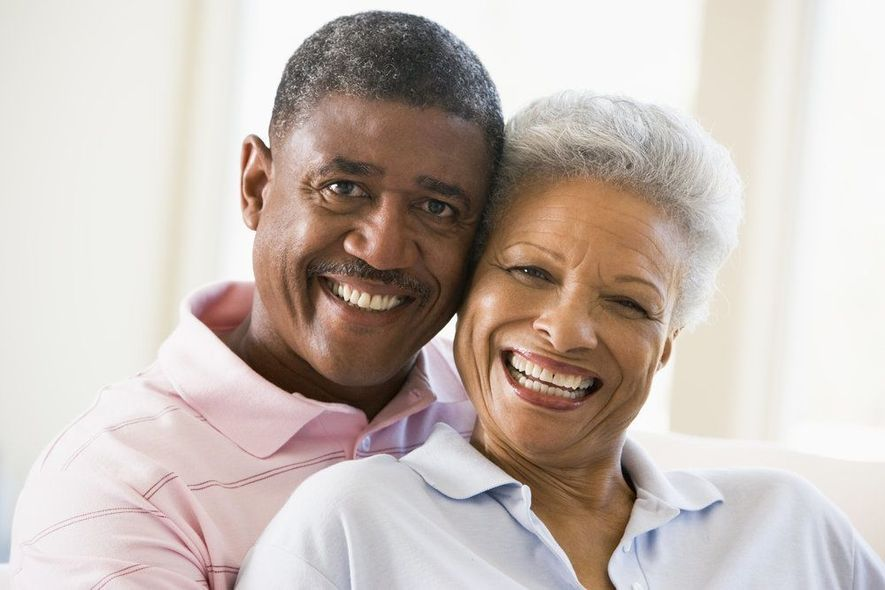 An older couple smiles together in the living room