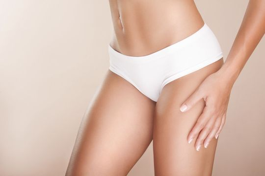 Woman's trim torso and legs in white underwear