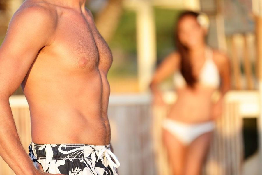 Close up of man's torso wearing swim trunks