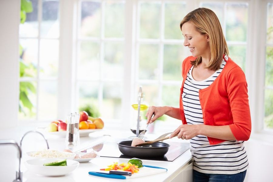 Happy woman cooking at stove